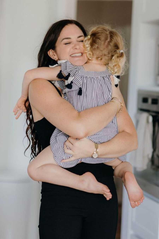 Mother wearing black hugging blonde daughter and smiling