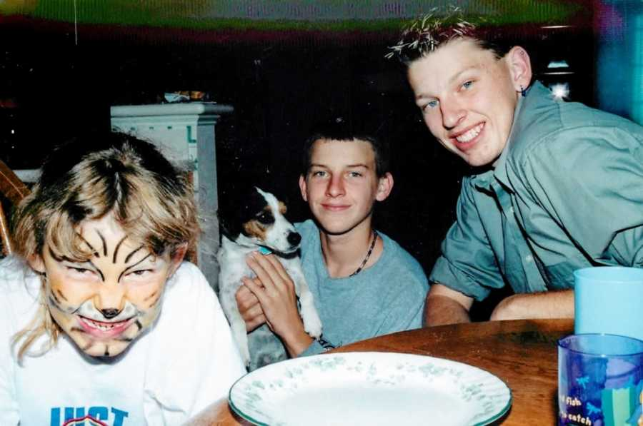 Young girl growls at the camera with tiger face paint on with her two brothers and family dog sitting beside her smiling