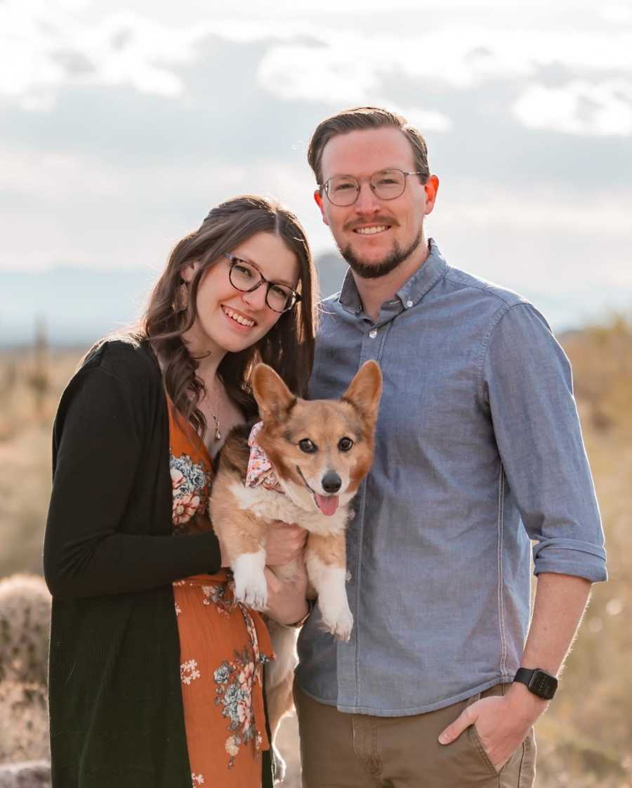 Woman poses for a family photo with her fiancé and their Corgi