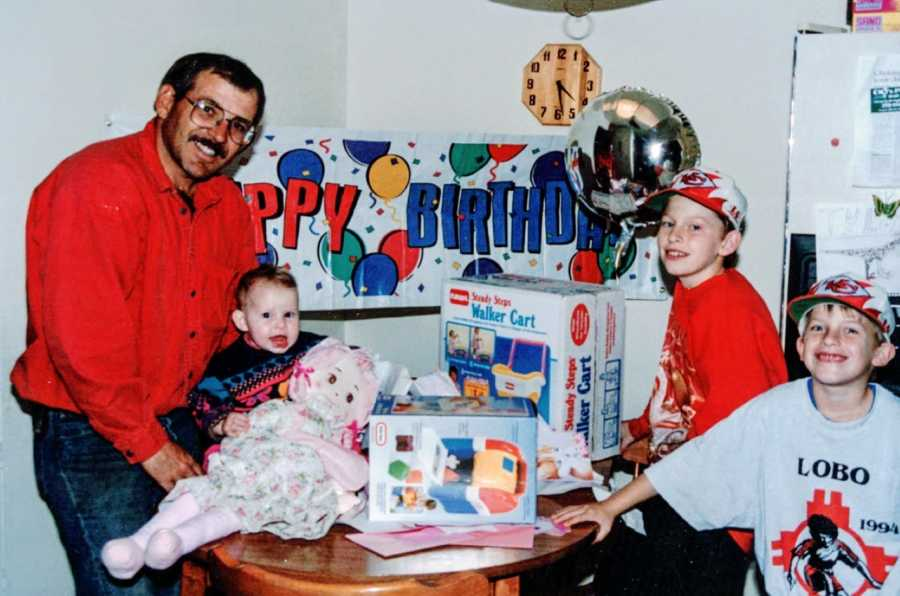 Three siblings pose with their father at a family birthday party