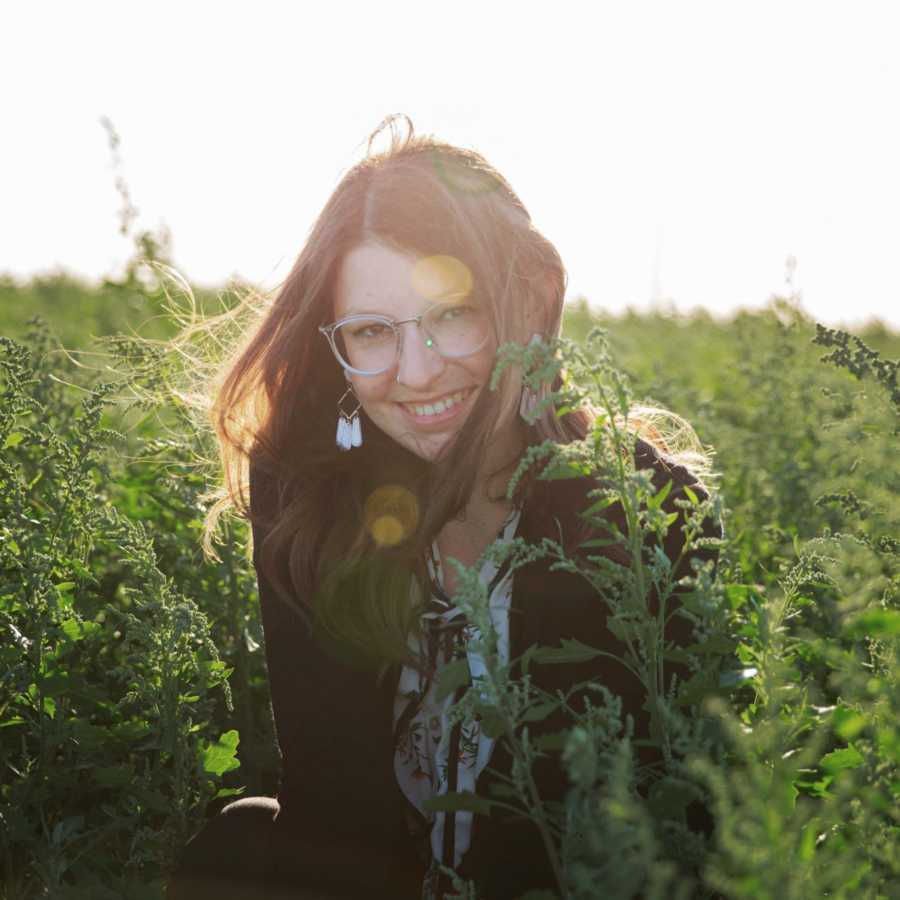 Woman with glasses on takes photo out in a field during a photoshoot