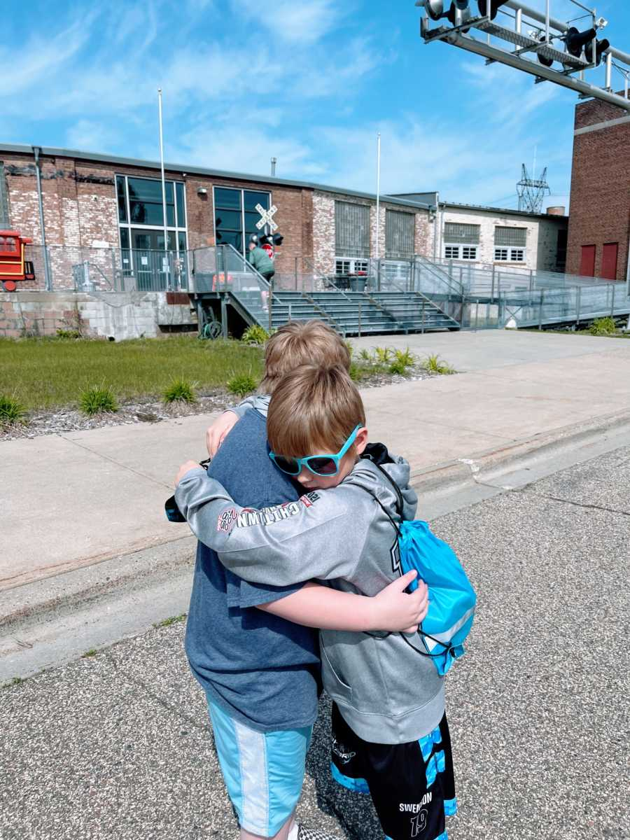 Two brothers hug each other while taking an outside stroll