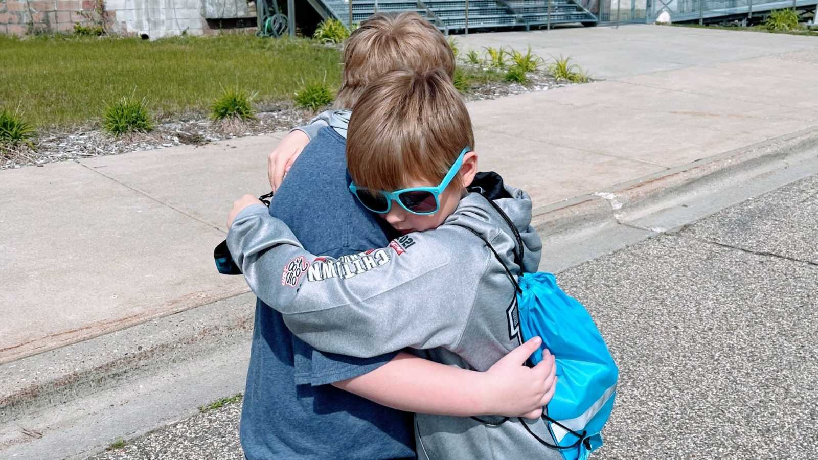 Two brothers embrace in a tight hug while on a walk outside