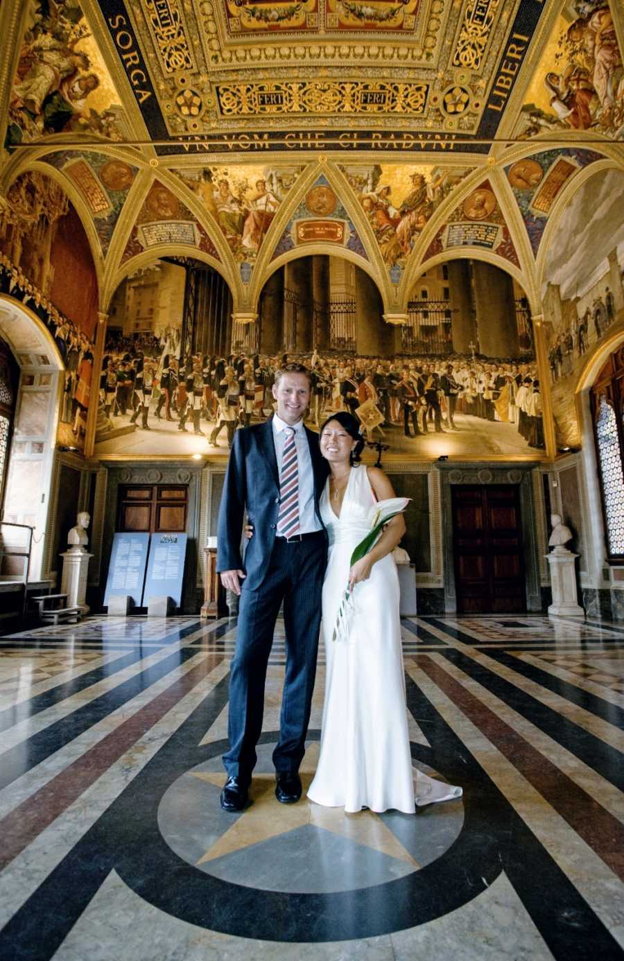 Interracial couple pose for a photo in a cathedral during their wedding