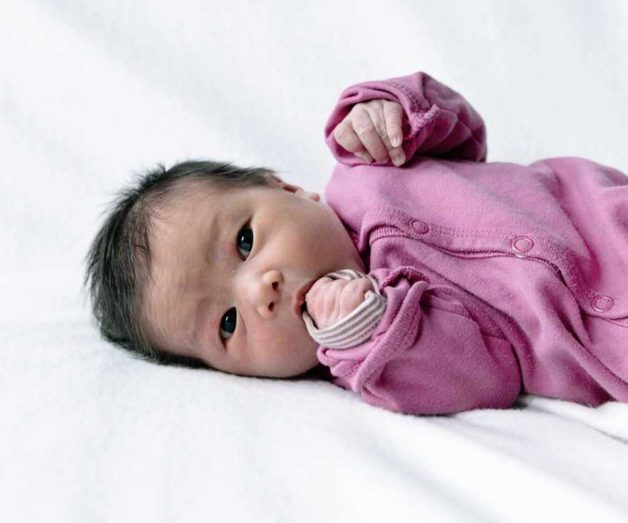 An infant girl in a pink onesie looks in the camera for a newborn photo