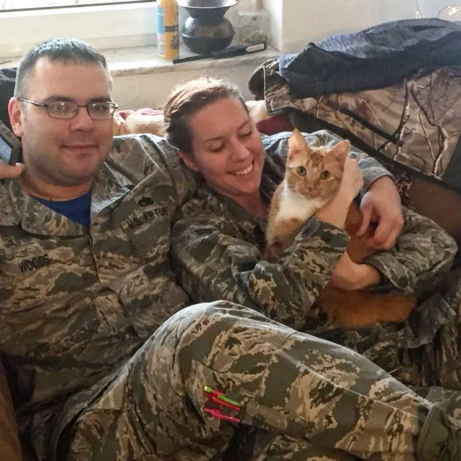 couple in military uniforms holding a cat