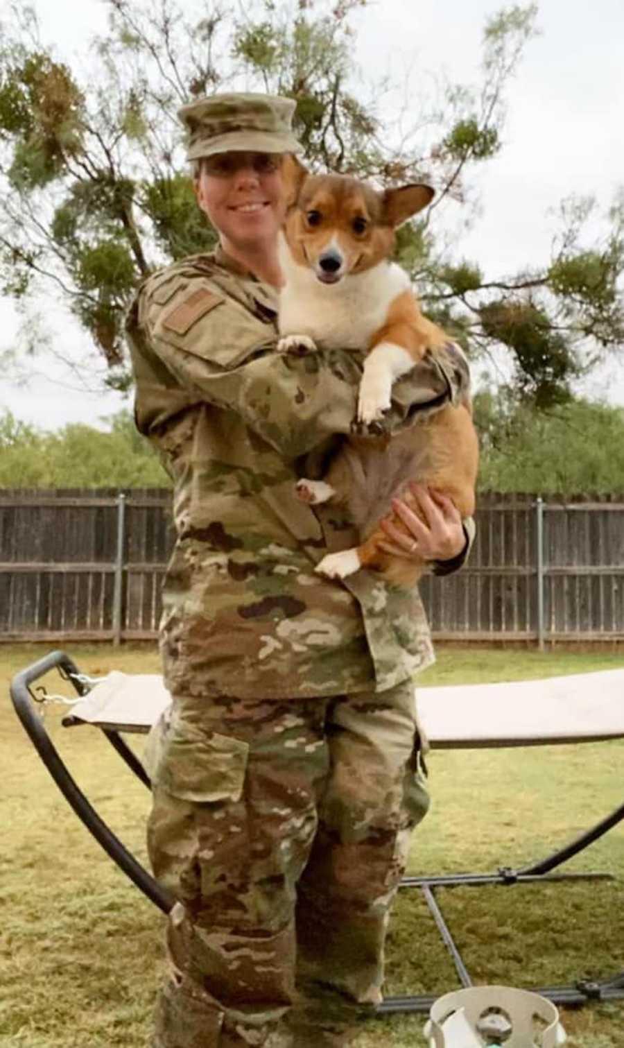 woman in military uniform holding a corgi