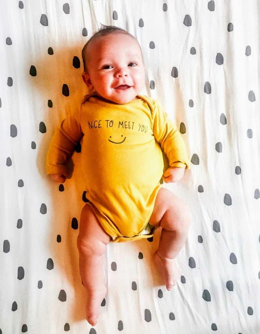 Baby wearing yellow onesie