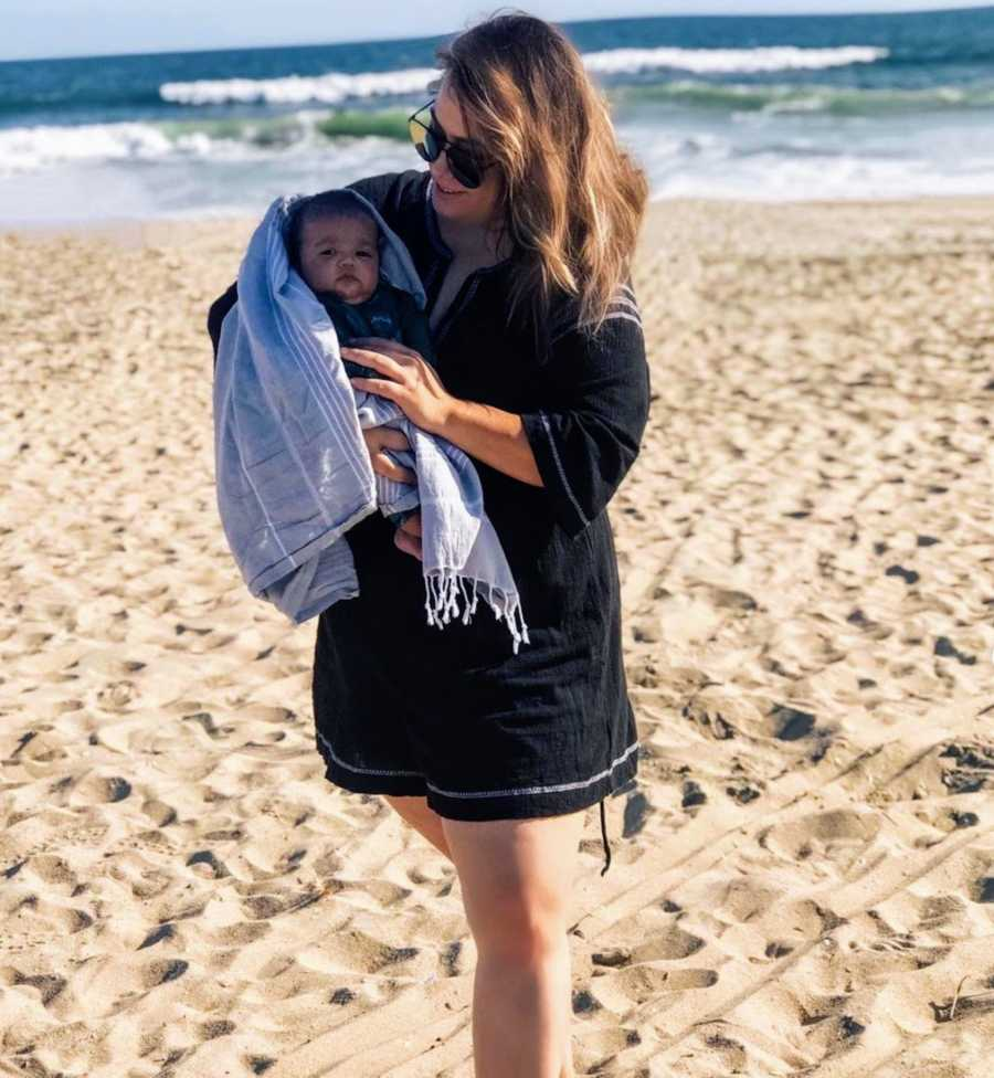 Mother holding baby on the beach