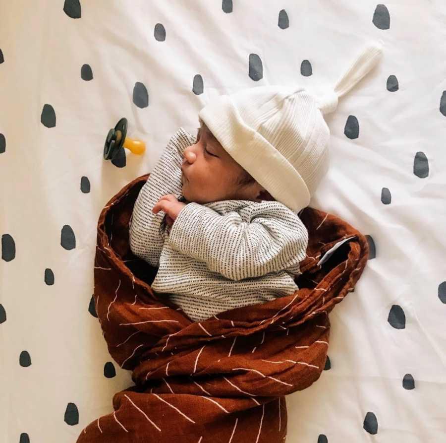 Newborn baby wearing hat swaddled in blanket