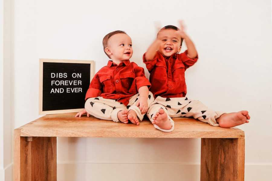 Brothers sitting on table beside a letterboard