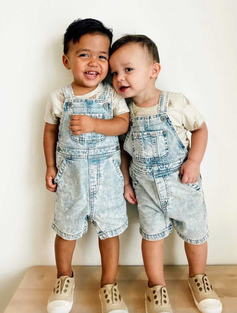 Brothers standing in front of white wall wearing overalls