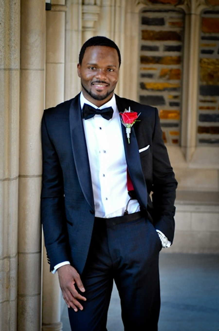 Man wearing black tuxedo with red rose smiling leaning against wall