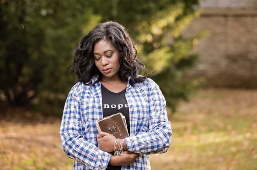 Woman standing by pine tree looking down holding a Bible
