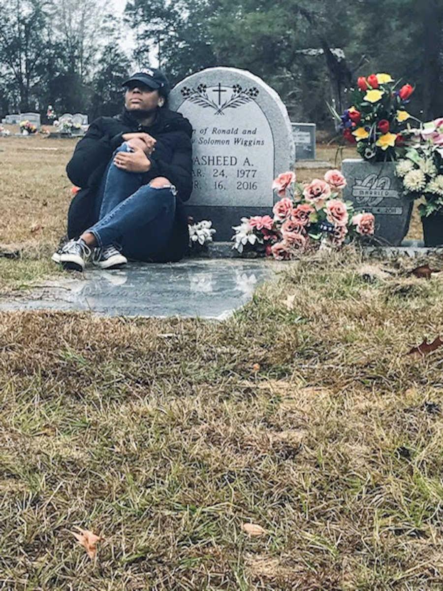 Woman wearing black hat sitting on a gravestone