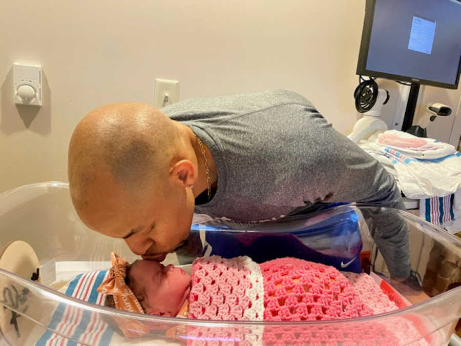 Man leaning down to kiss newborn daughter wrapped in pink blanket