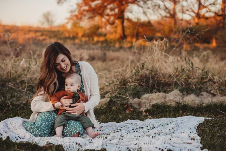 Woman smiles down at her baby boy during an outside photoshoot at sunset
