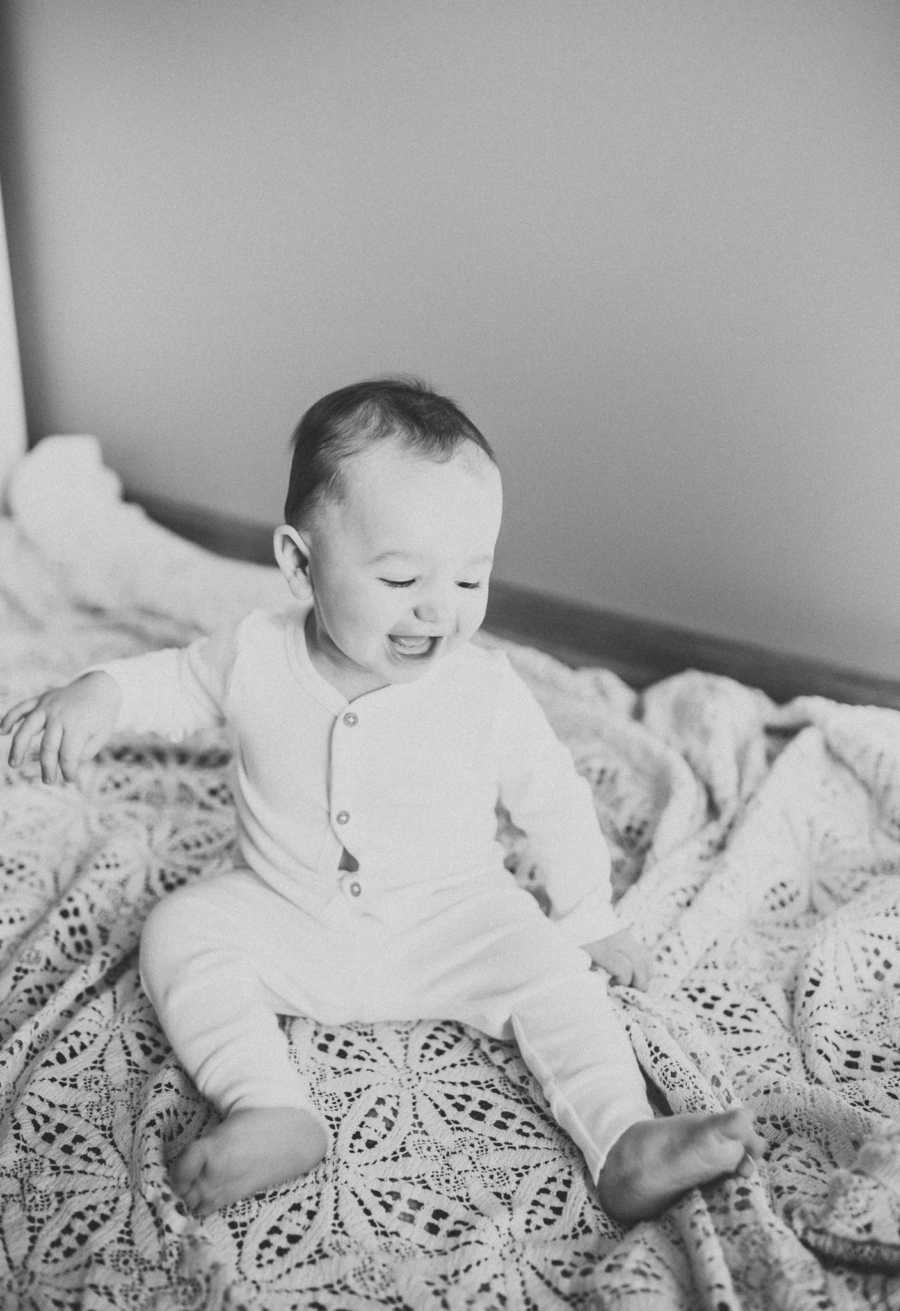 Black-and-white photo of an 18-month baby in a white onesie