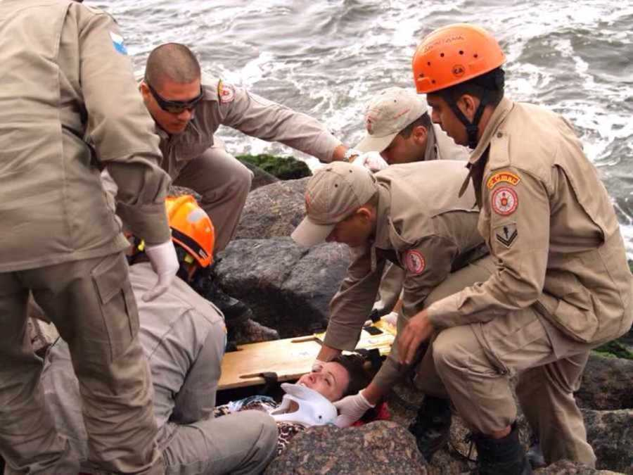 Woman being rescued from rocks