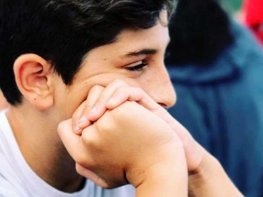Close up of teen son looking off camera while resting his face in his hands