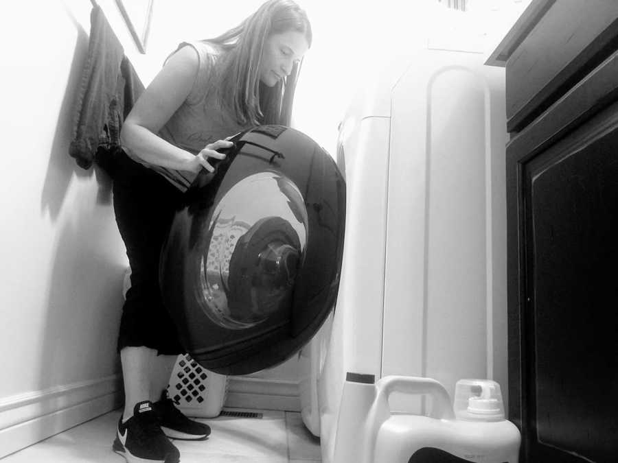 Mom bends down to load the dryer while doing household chores