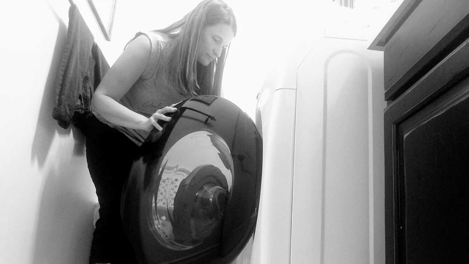 Mom snaps a photo while she finishes loading the laundry by herself