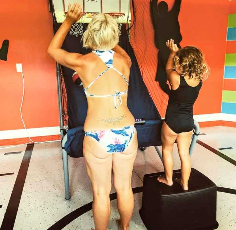 Mom of three plays arcade basketball in swimwear while her young daughter cheers her on