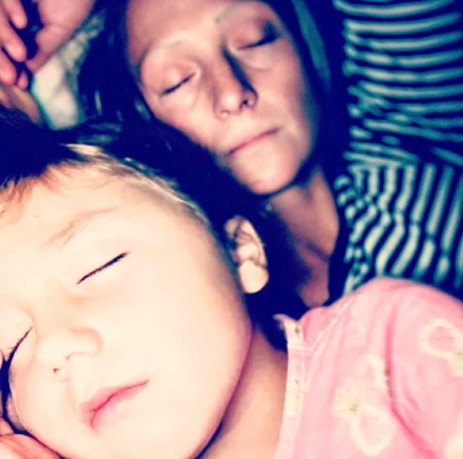 Mom sleeps peacefully with her son after a rough day