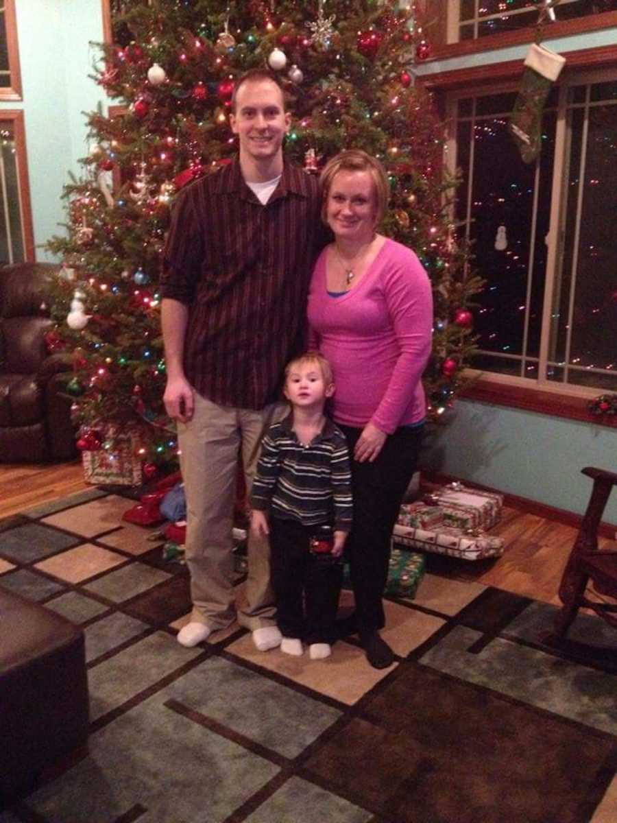 couple and son by Christmas tree