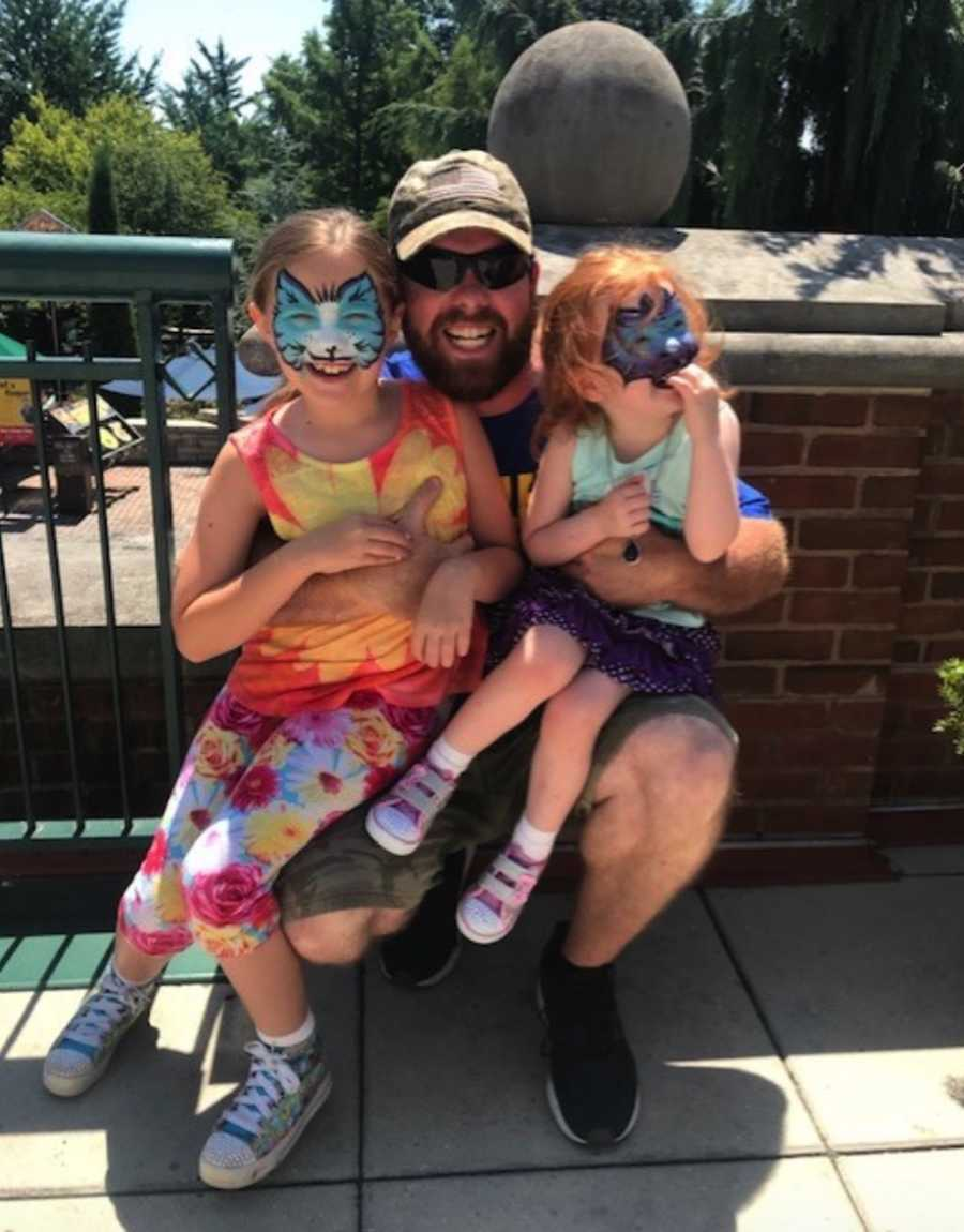 Dad with daughters at theme park with face paint