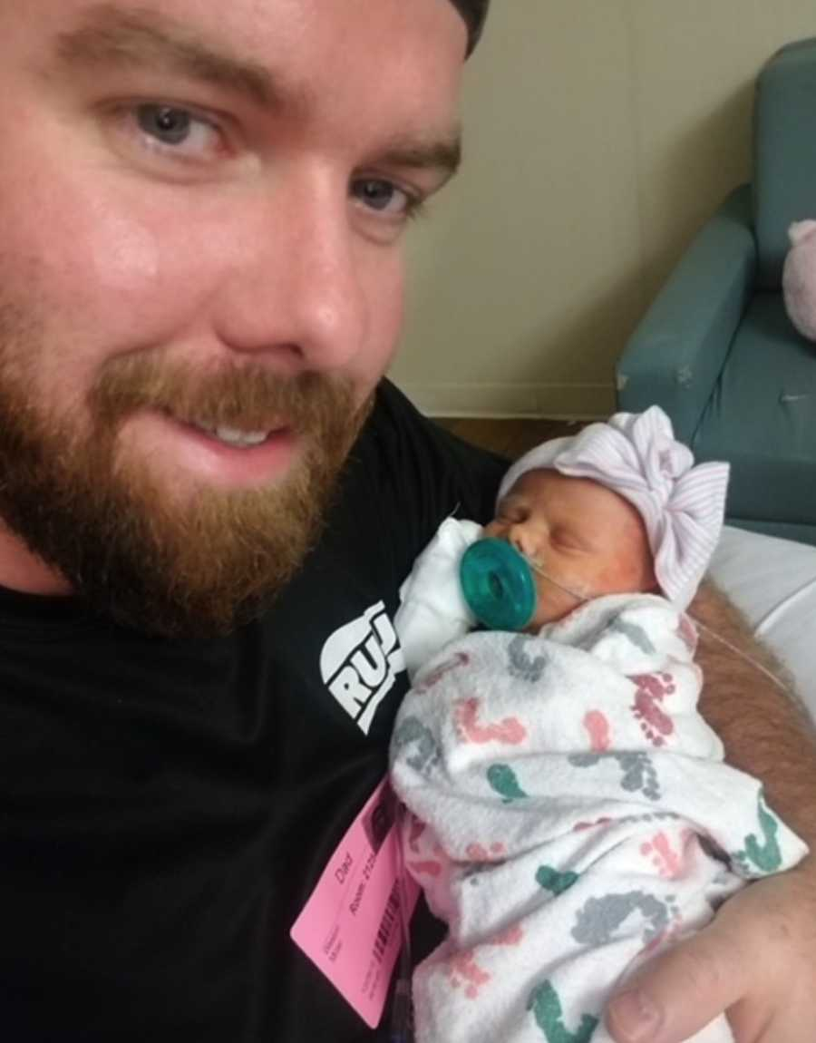 Father holding newborn daughter