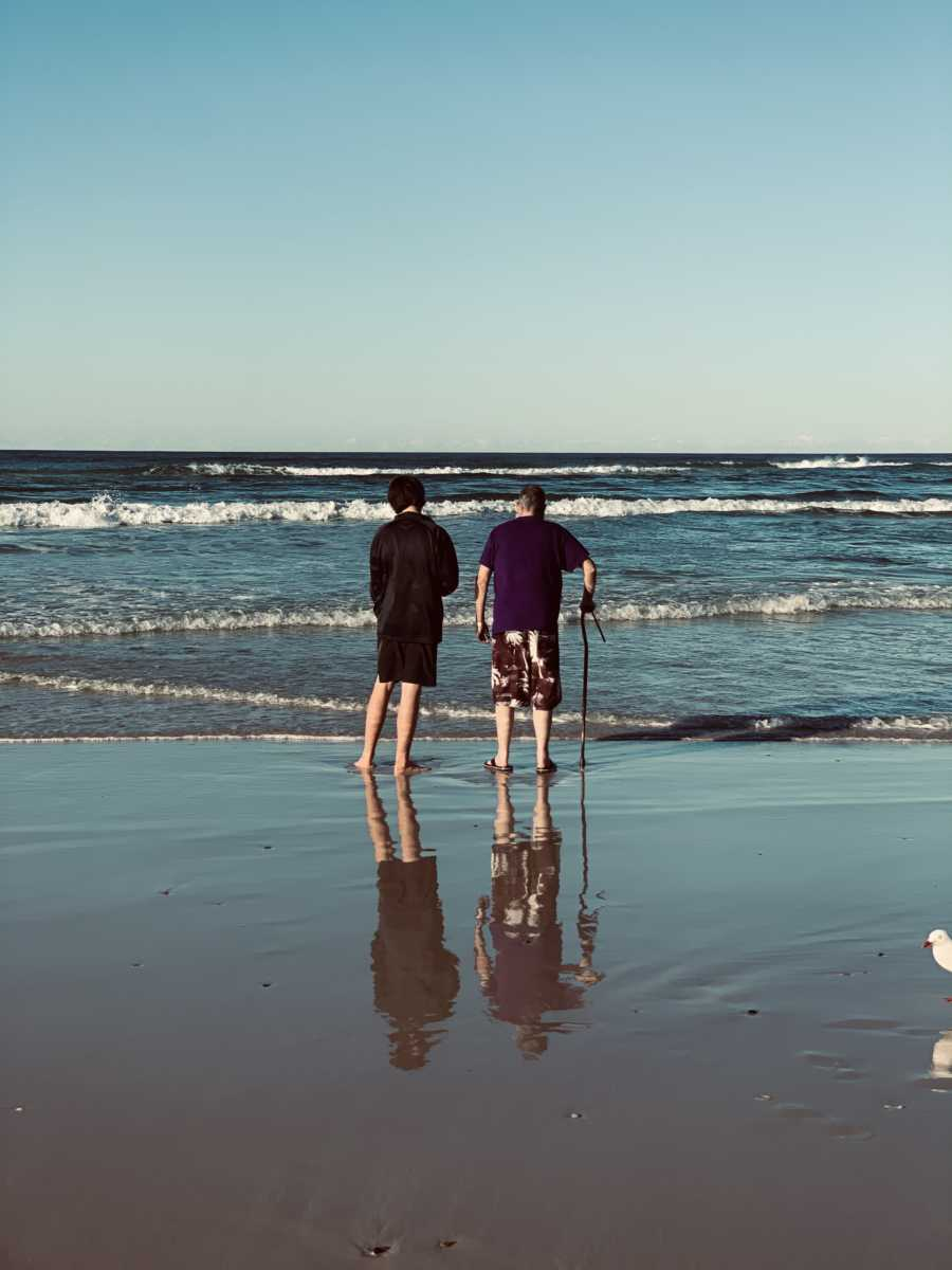 Dying man using cane feels the ocean lap at his feet