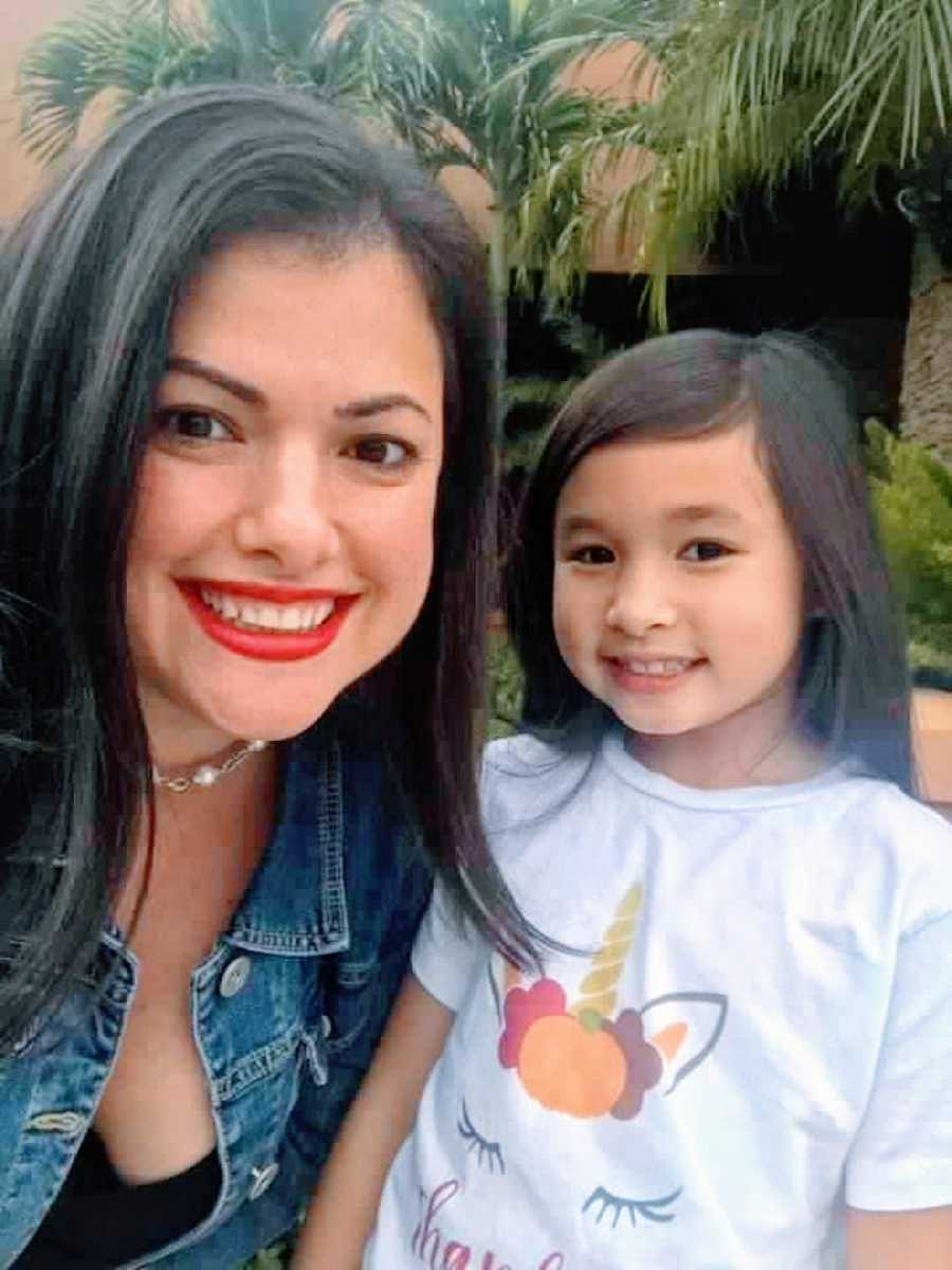Woman wearing bright red lipstick takes a selfie of her and her 10-year-old daughter