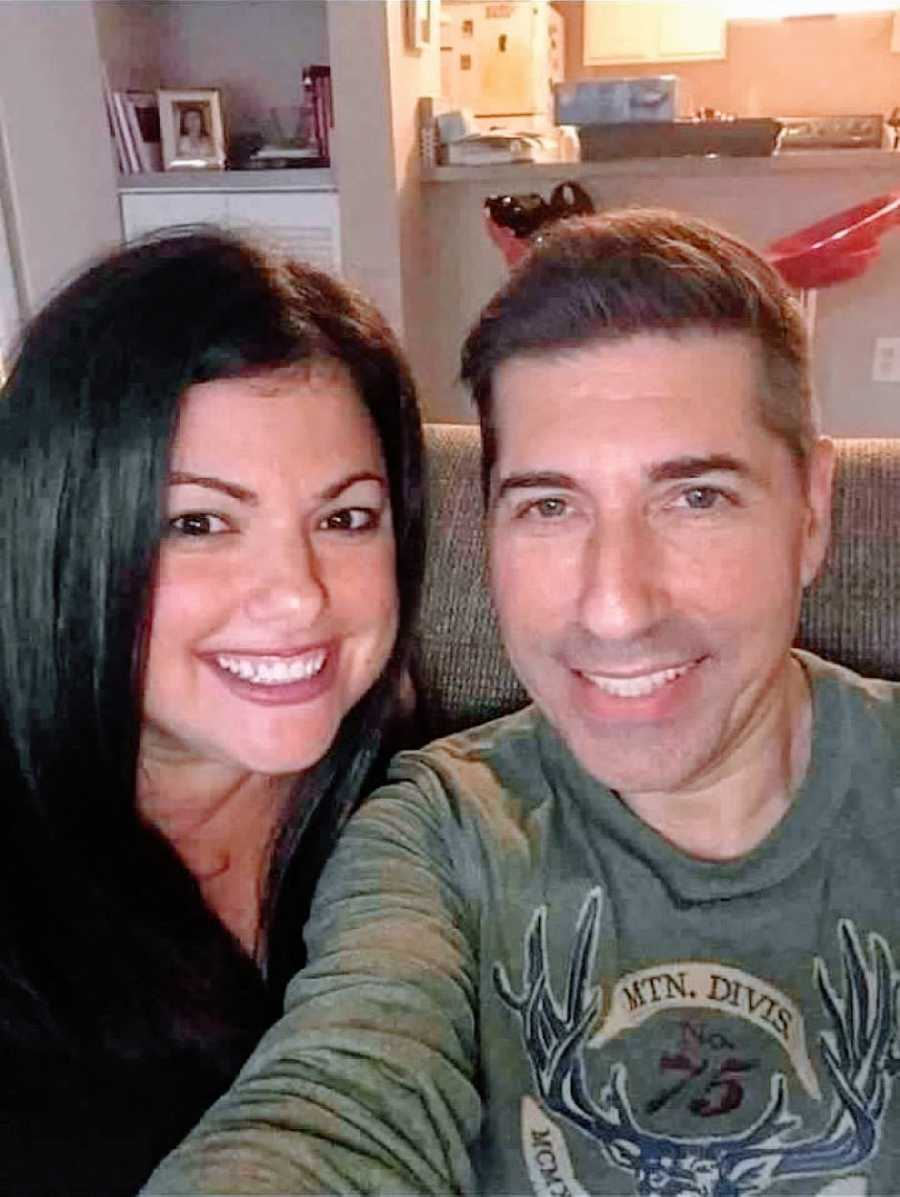 Couple take selfie while snuggling up at home on the couch