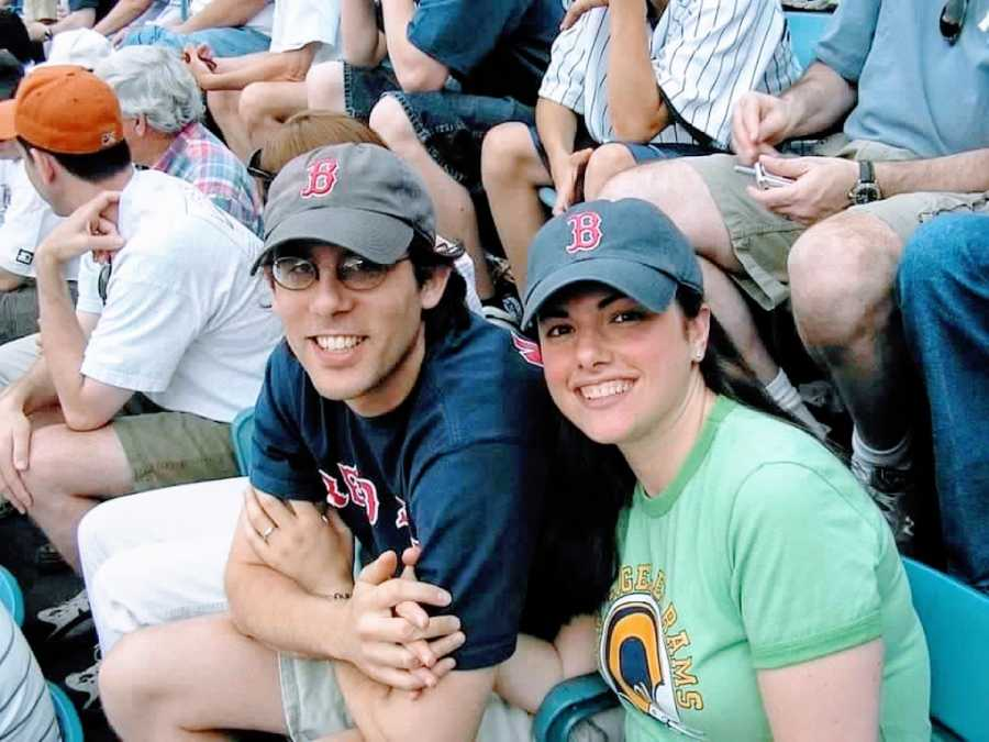 Woman poses with her then-husband at a baseball game in matching Boston Red Sox hats
