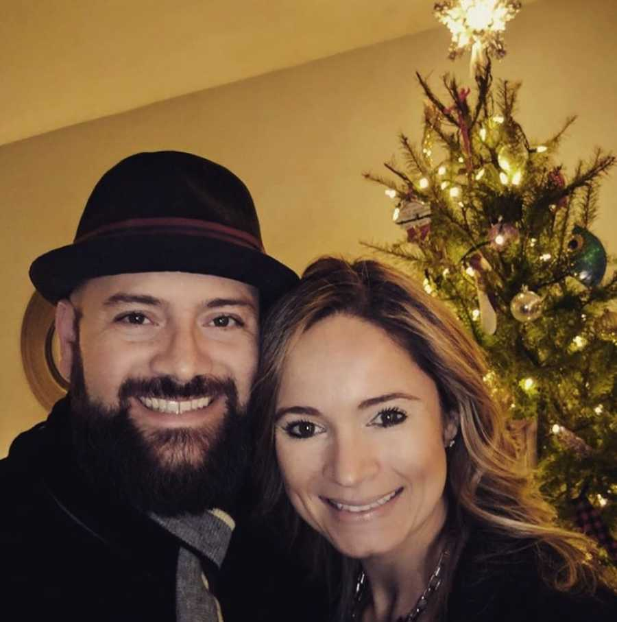 Couple smiling with Christmas tree