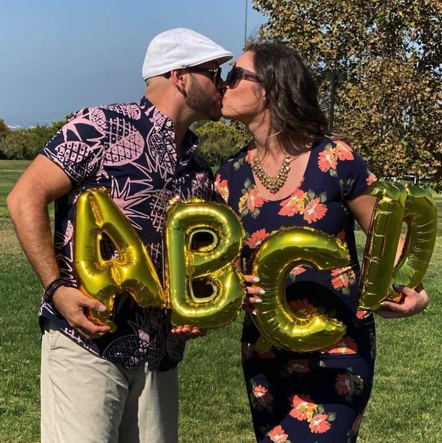 Couple kissing at quadruplet pregnancy announcement