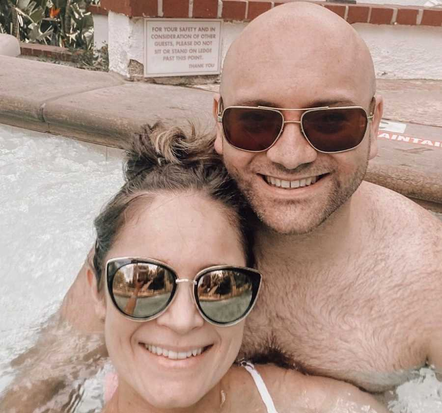Couple smiling in pool wearing sunglasses