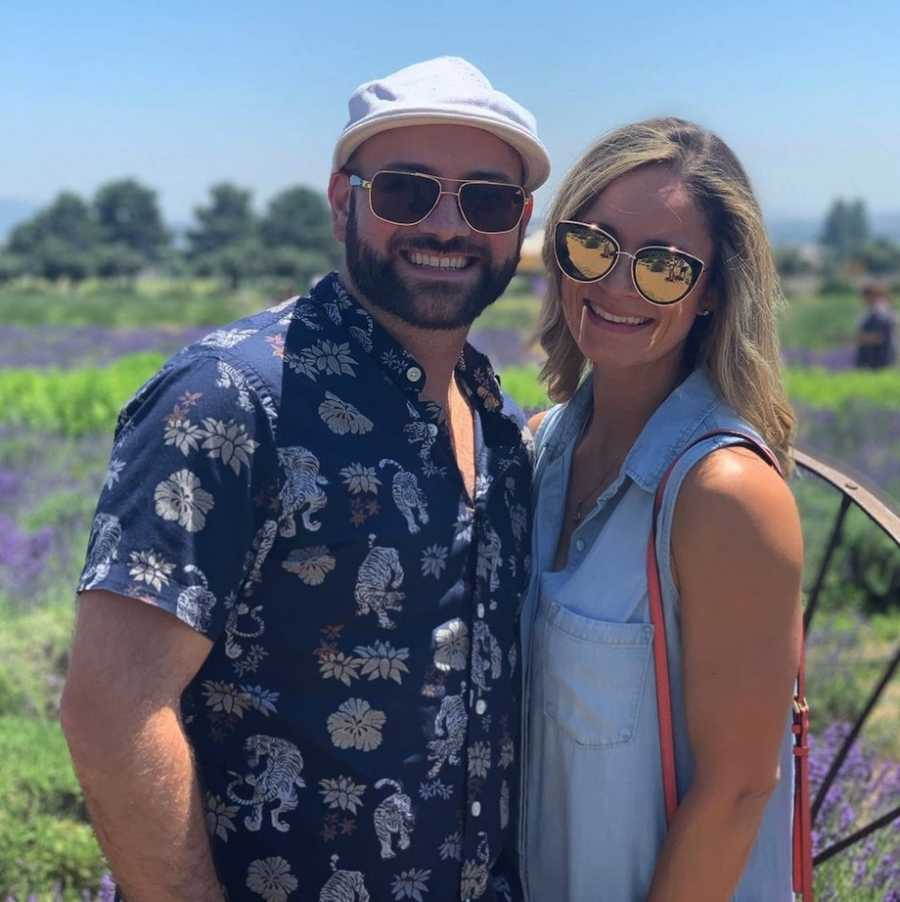 Couple smiling in lavender field wearing sunglasses