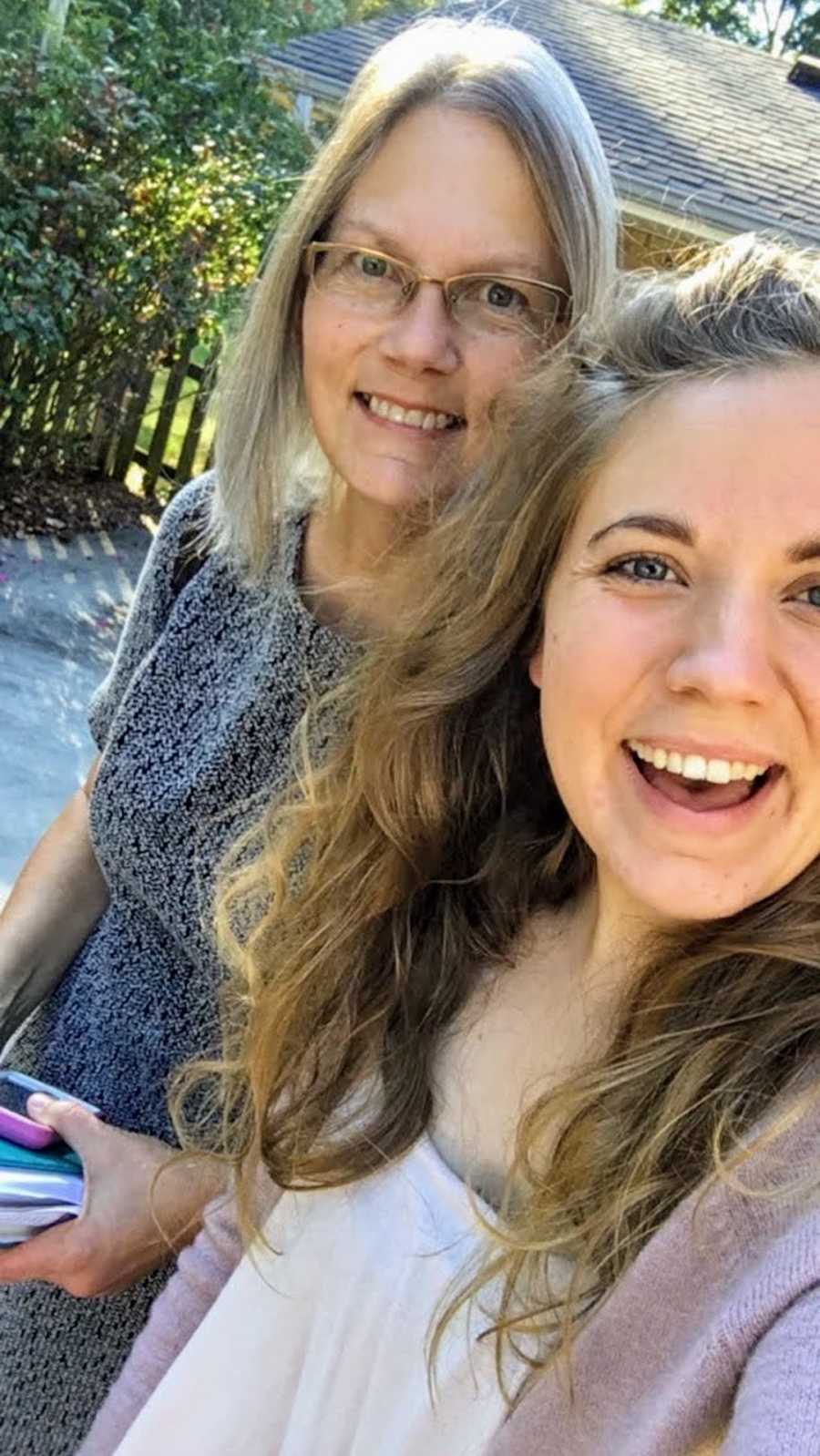 Mother and daughter outside taking smiling selfie
