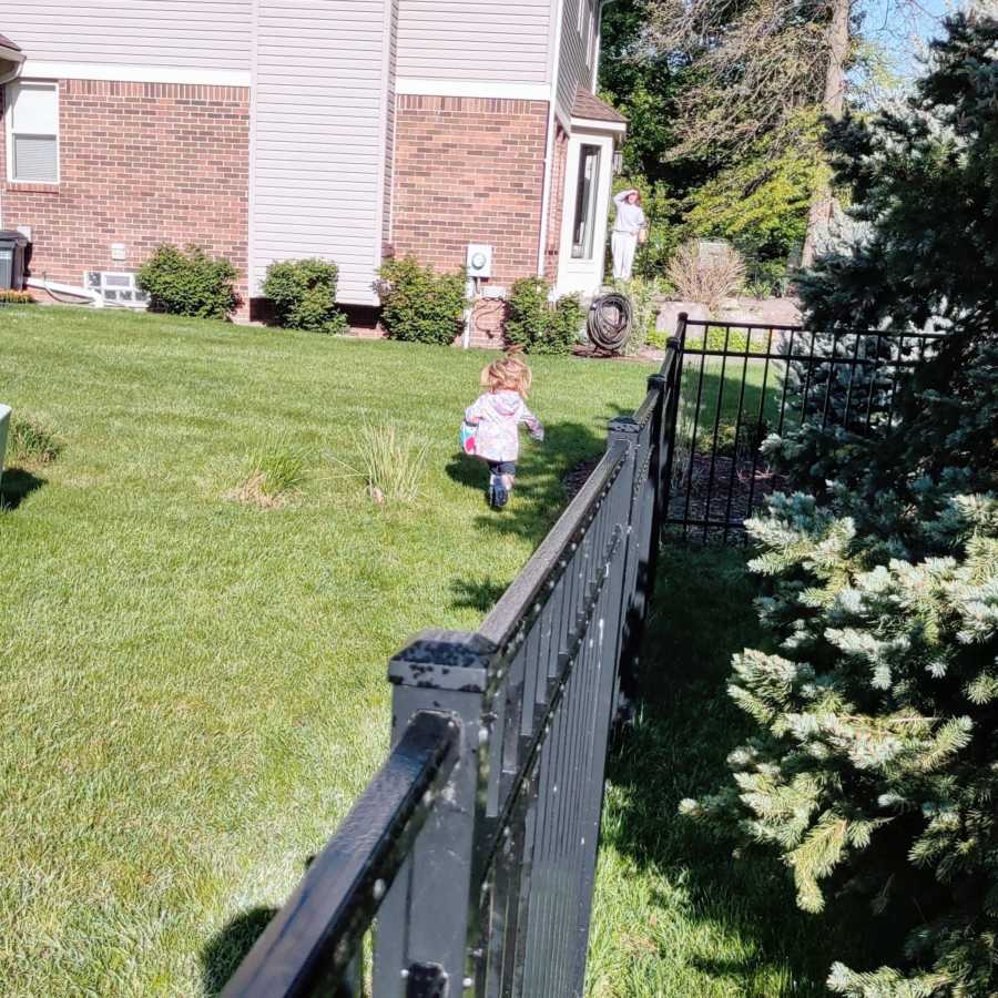 Little girl runs to greet her neighbor and babysitter on a sunny day