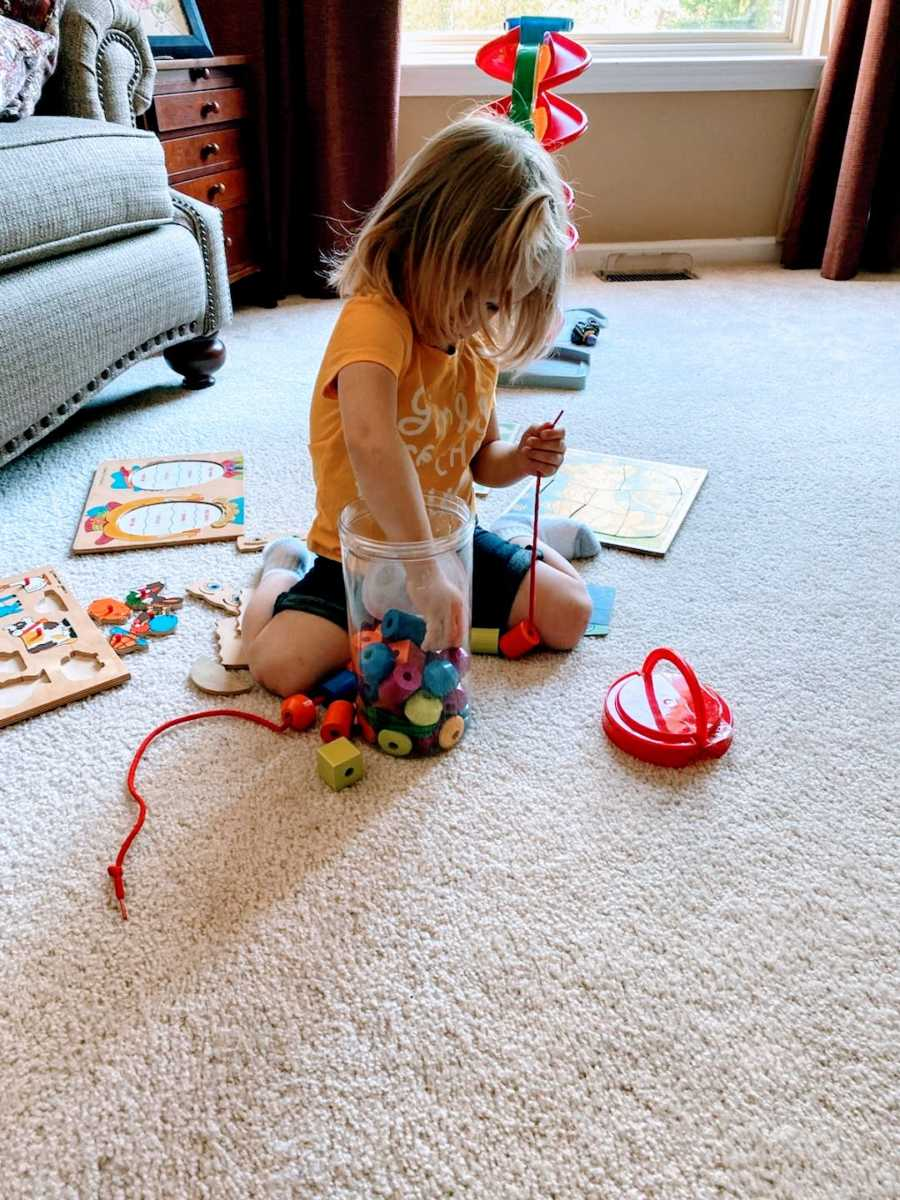 Young toddler concentrates on building a toy out of building blocks while being babysat
