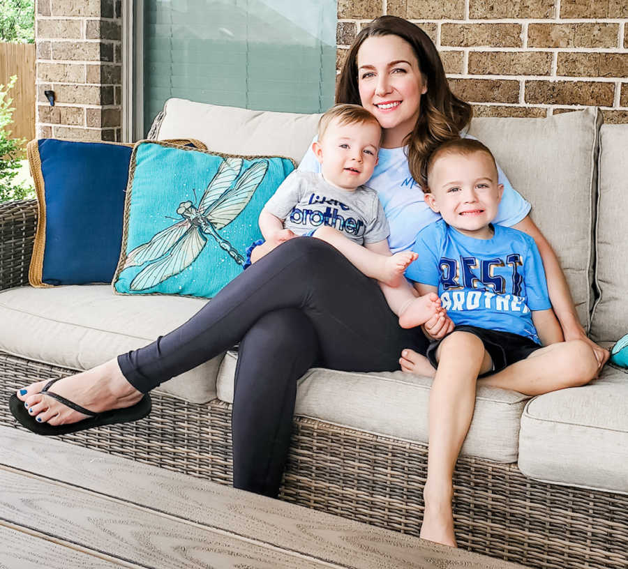 mom holding two sons on couch