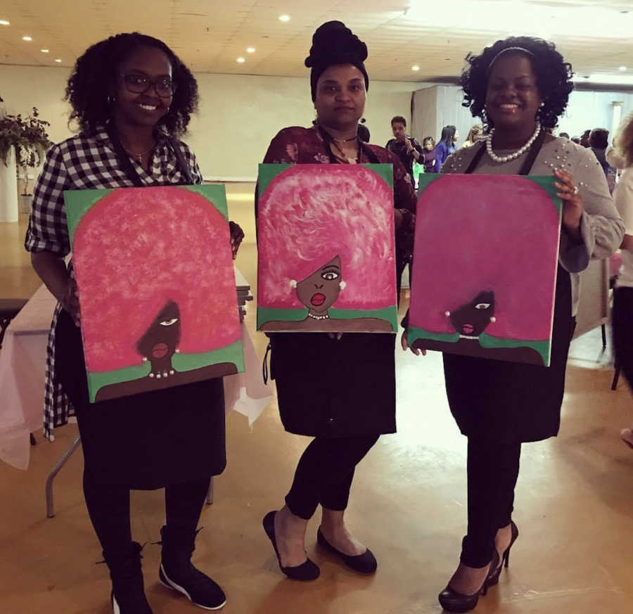three women standing together with paintings