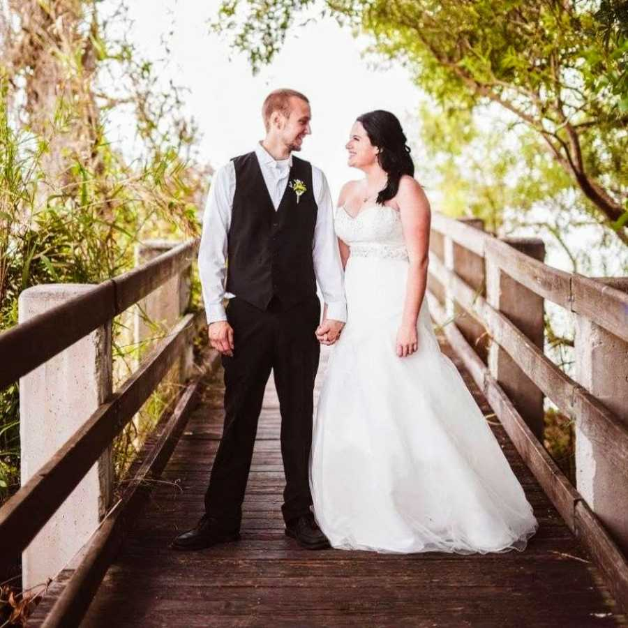 Newly married couple pose for an outdoor photo on a bridge while smiling at each other