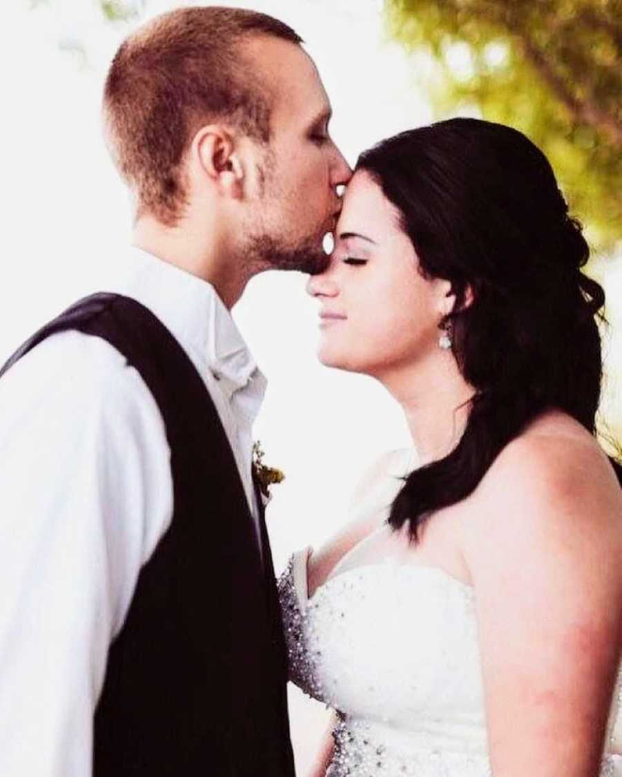Husband kisses his new wife on the forehead during wedding photoshoot