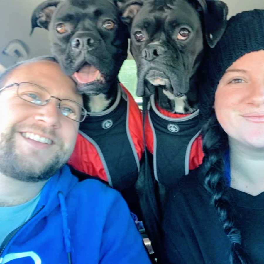 Married couple take a car selfie with two black boxers