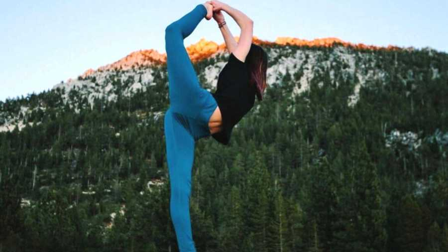 Woman in yoga pose in front of a mountain