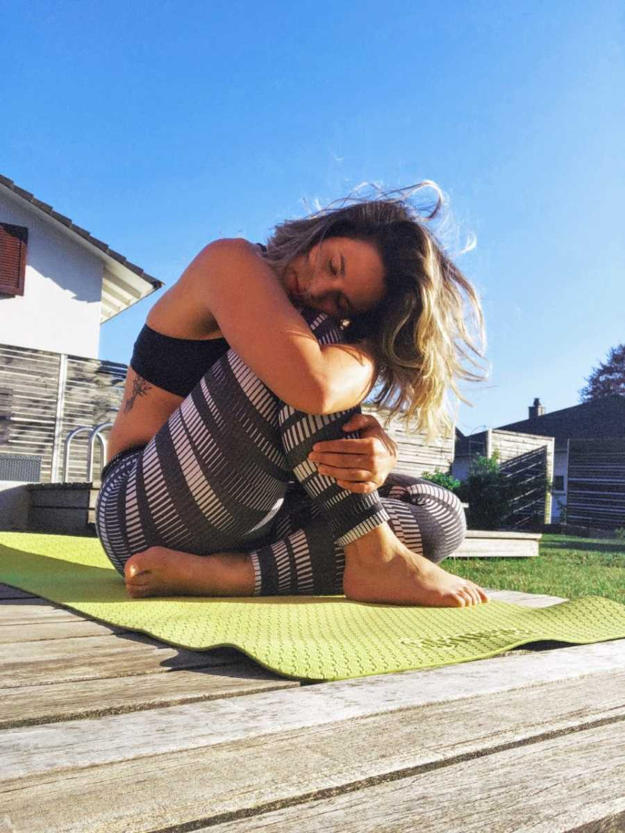 Woman hugs herself while practicing yoga on a green yoga mat out in the sunshine