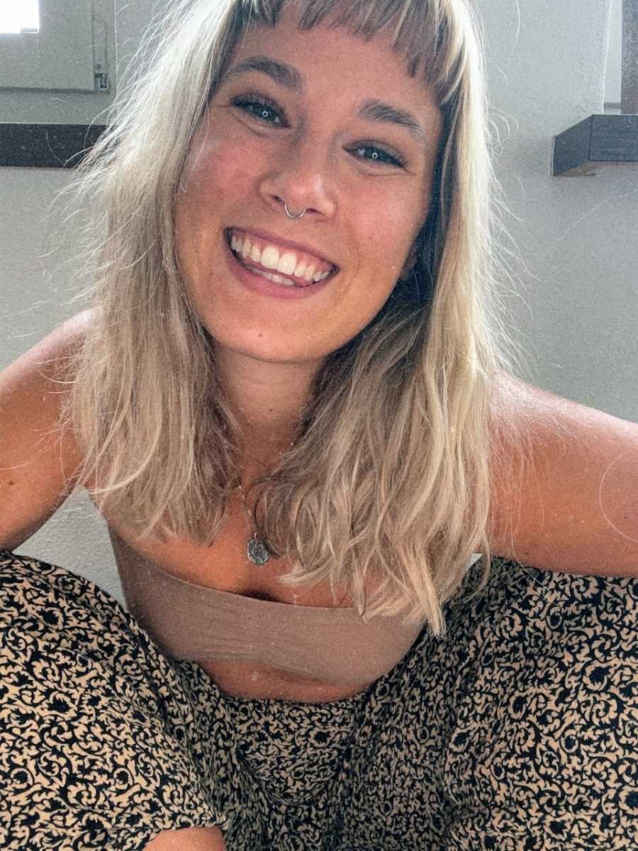 Woman in trendy outfit takes a cute selfie with a big smile